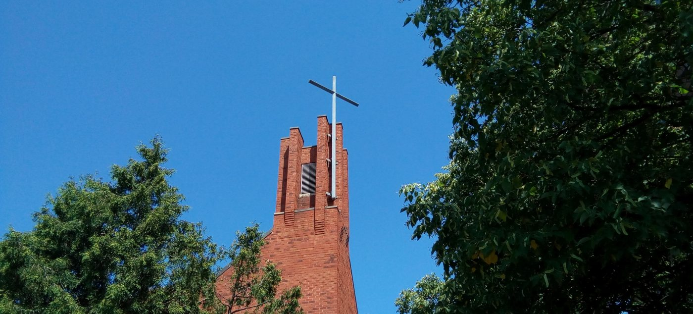 St Elizabeth church steeple against a blue sky and trees on its left and right